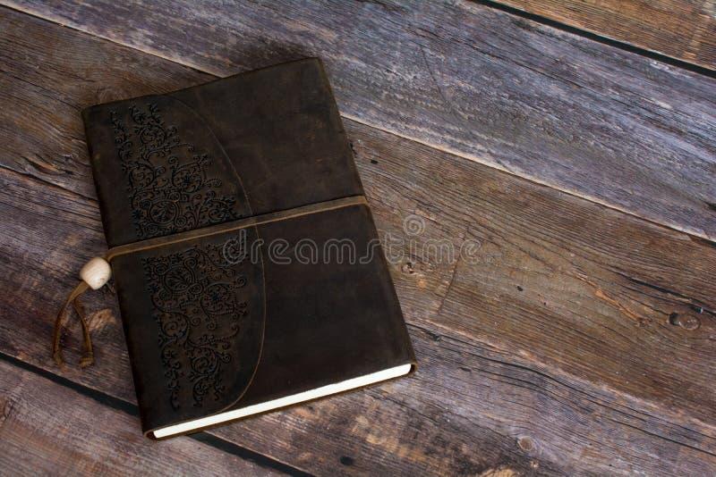 Libro rilegato del giornale del cuoio classico su una vecchia fine del pavimento del bordo del granaio su fotografia stock libera da diritti