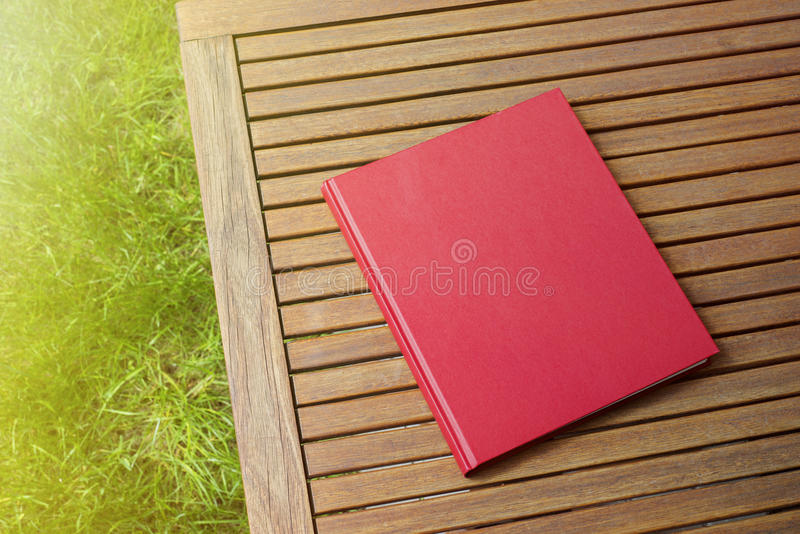 Libro rojo en la tabla al aire libre en la cafetería foto de archivo