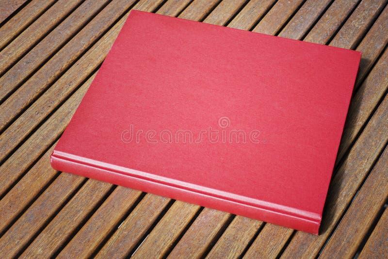 Libro rojo en la tabla al aire libre en la cafetería imagen de archivo libre de regalías