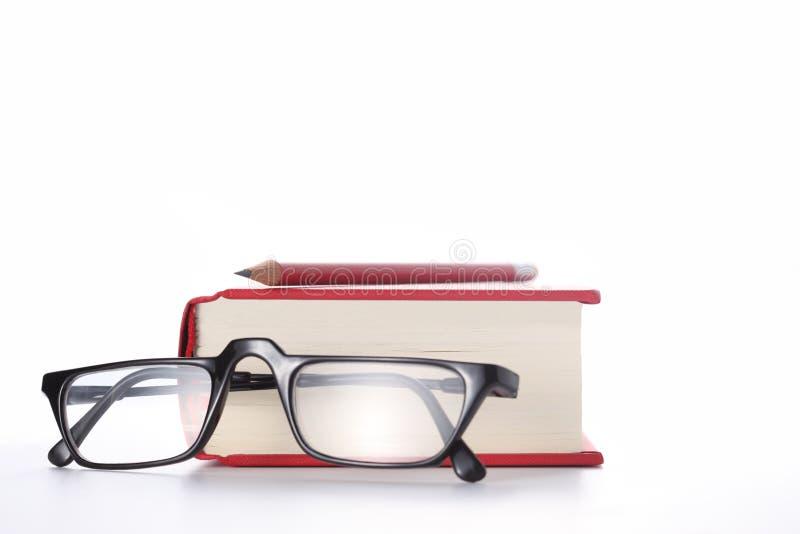 Libro rojo, vidrios del ojo y un lápiz rojo aislado en el fondo blanco con el espacio de la copia para su texto foto de archivo