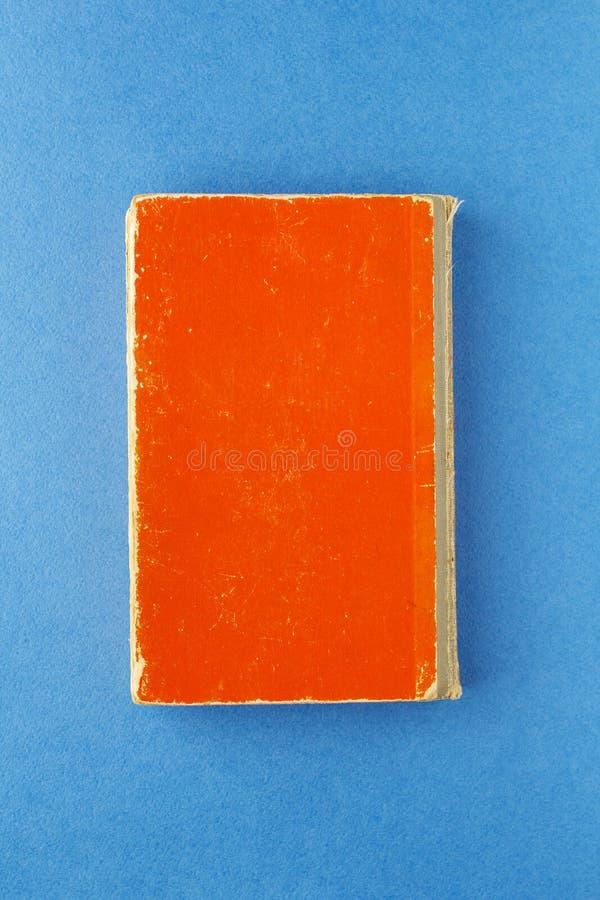 libro rojo viejo en un fondo azul brillante imagenes de archivo