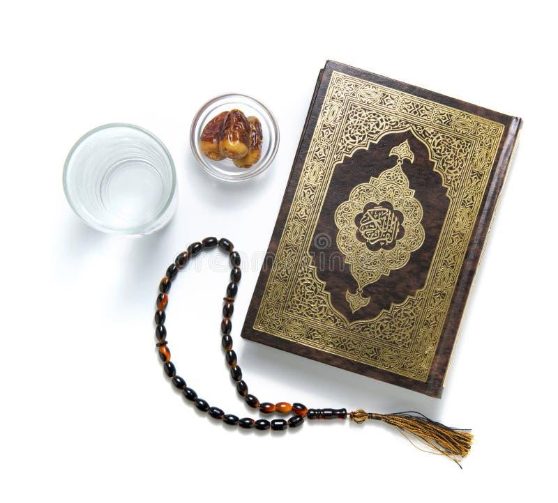 Libro sacro, acqua, date e rosario di Corano, isolati su bianco immagini stock libere da diritti