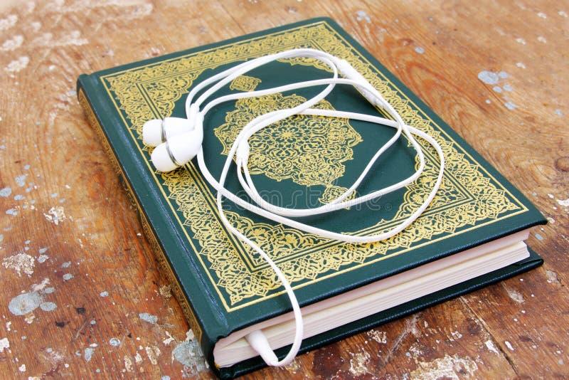 Libro sagrado islámico del Corán con concepto de las auriculares foto de archivo