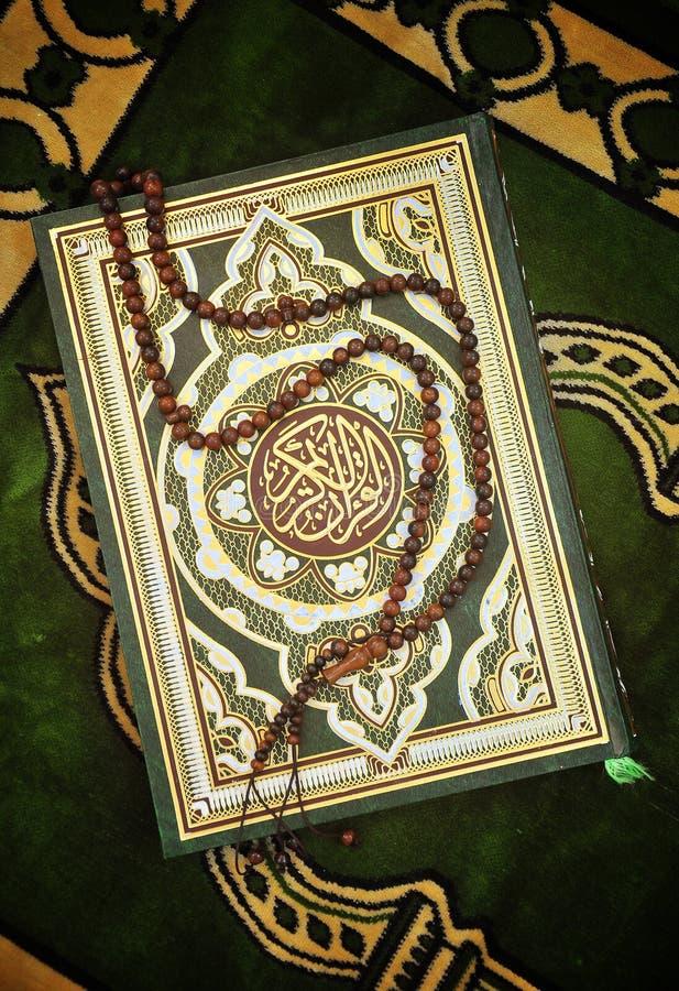 Libro santo del Quran con il rosario immagini stock