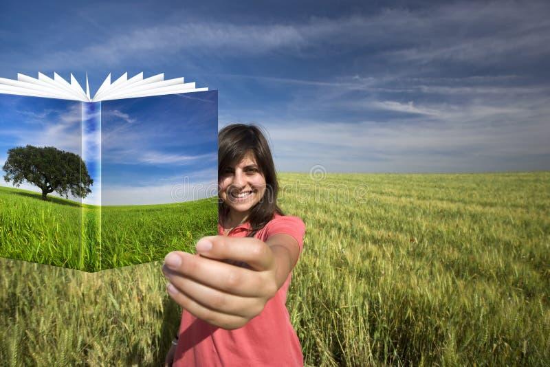 Libro sonriente de la explotación agrícola de la mujer joven foto de archivo libre de regalías