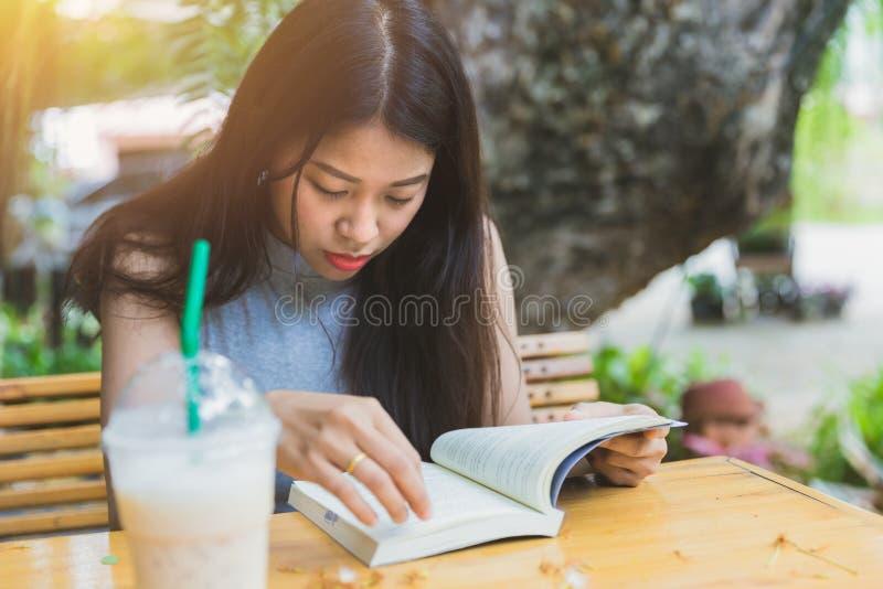 Libro tascabile serio della lettura della donna asiatica fotografia stock libera da diritti