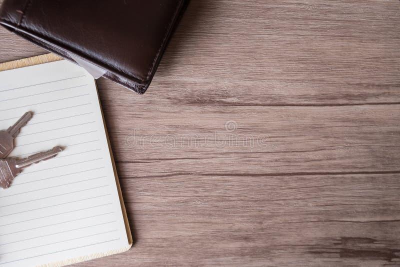Libro vacío y llave y cartera en la tabla de madera, espacio de la copia fotografía de archivo