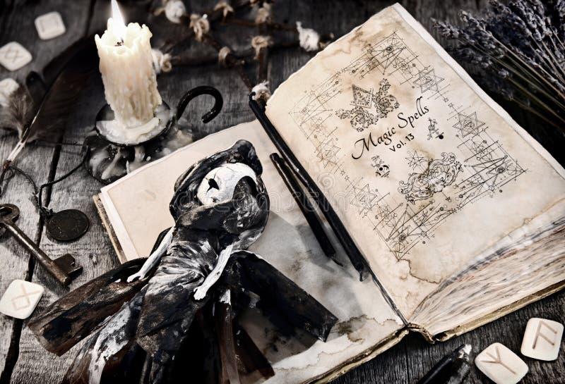 Libro viejo con encantos malvados, la muñeca asustadiza, la runa y la vela ardiente en tablones foto de archivo libre de regalías