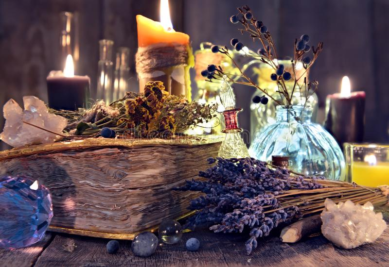 Libro viejo de la bruja con las flores de la lavanda, el cristal y las velas del mal fotografía de archivo