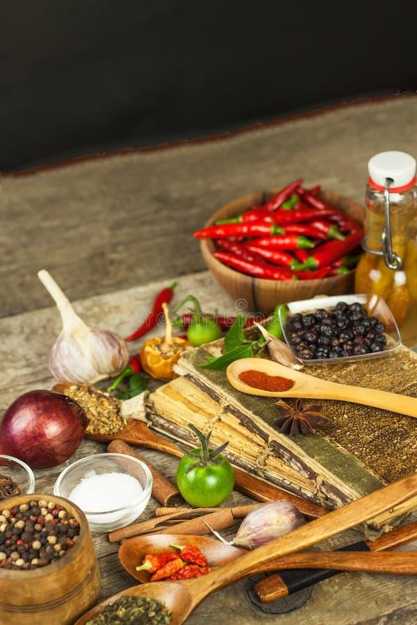 Libro viejo de las recetas de la cocina El fondo y la receta culinarios reservan con las diversas especias en la tabla de madera fotos de archivo libres de regalías