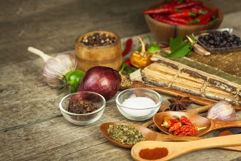 Libro viejo de las recetas de la cocina El fondo y la receta culinarios reservan con las diversas especias en la tabla de madera foto de archivo