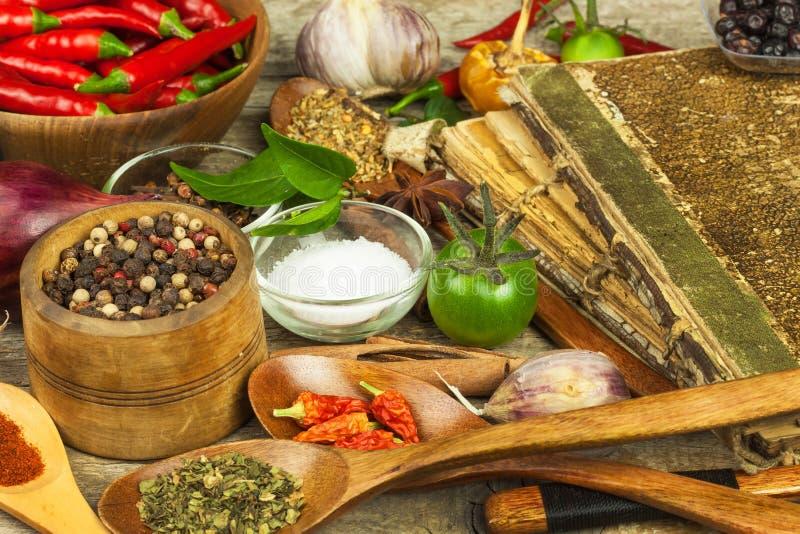 Libro viejo de las recetas de la cocina El fondo y la receta culinarios reservan con las diversas especias en la tabla de madera fotos de archivo