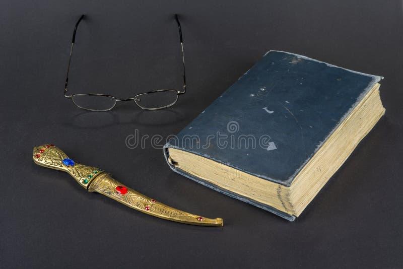 Libro viejo del vintage con el cuchillo del otomano en un negro foto de archivo