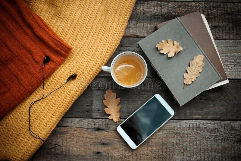 Libro viejo, teléfono elegante, hojas de otoño en fondo de madera Concentrado fotos de archivo libres de regalías
