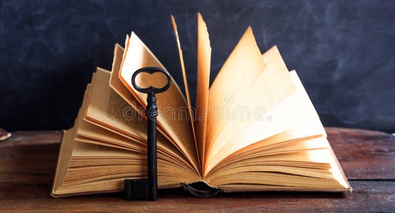 Libro viejo y una llave en un escritorio de madera foto de archivo