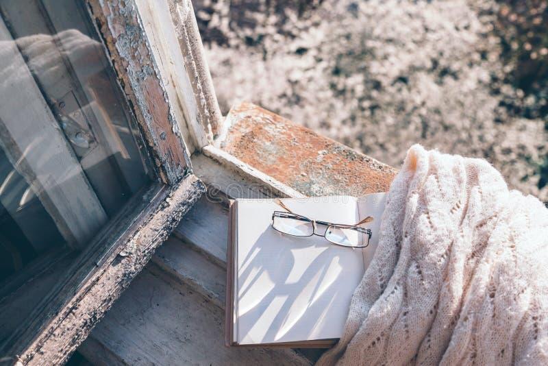 Libro y café en travesaño de la ventana sobre árbol de la primavera fotografía de archivo