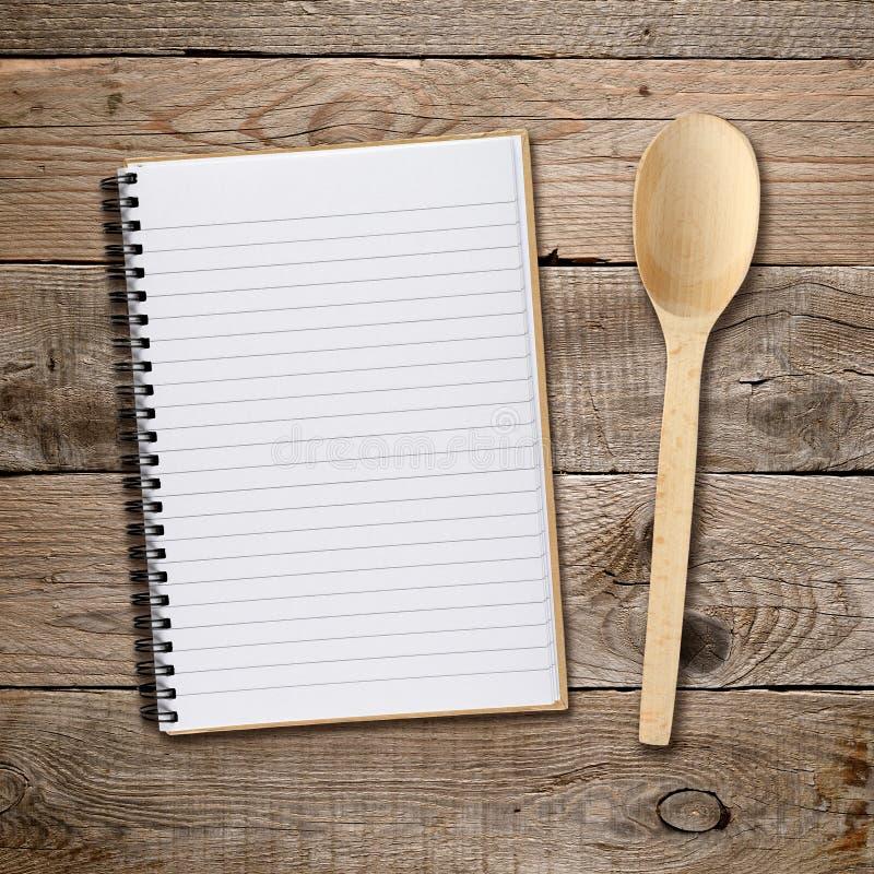Libro y cuchara de la receta foto de archivo