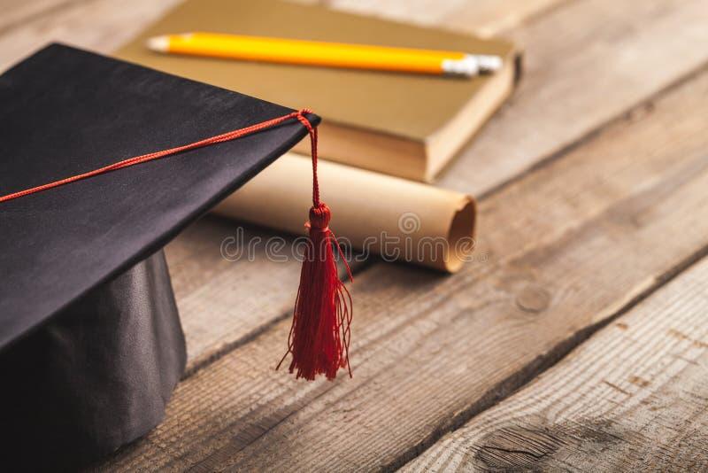 Libro y diploma del sombrero de la graduación en de madera imagen de archivo libre de regalías