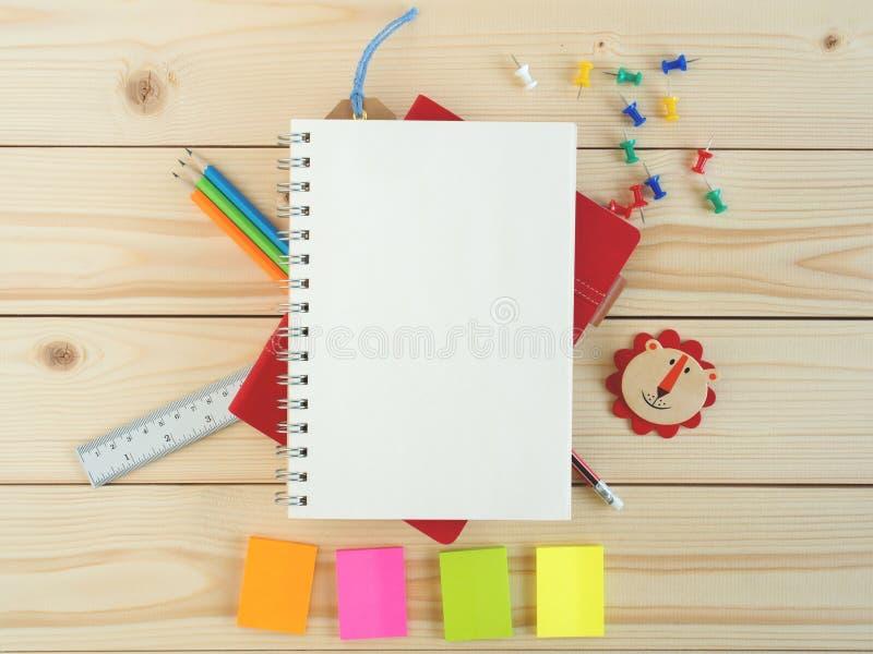 Libro y efectos de escritorio en blanco en la tabla de madera imagenes de archivo