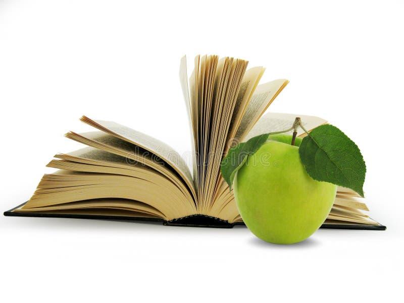Libro y manzana verde imagen de archivo