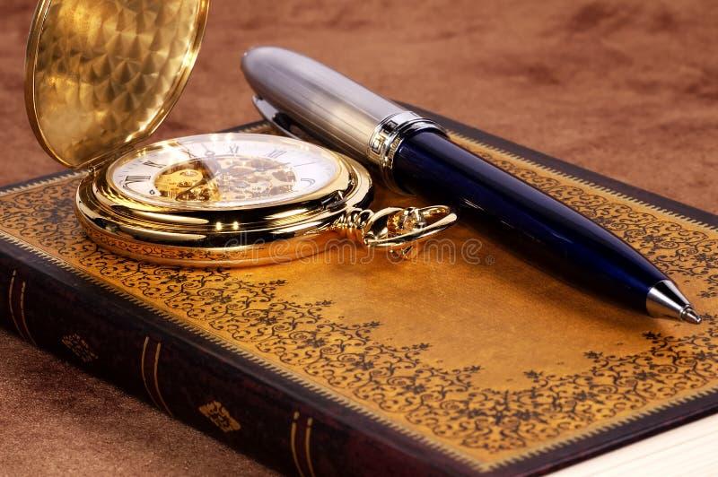 Libro y reloj foto de archivo