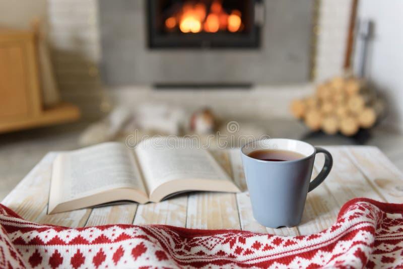 Libro y taza de té cerca de la chimenea imagen de archivo