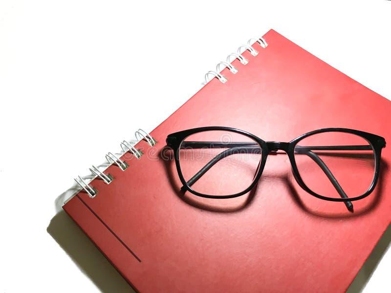 Libro y vidrios rojos imagen de archivo