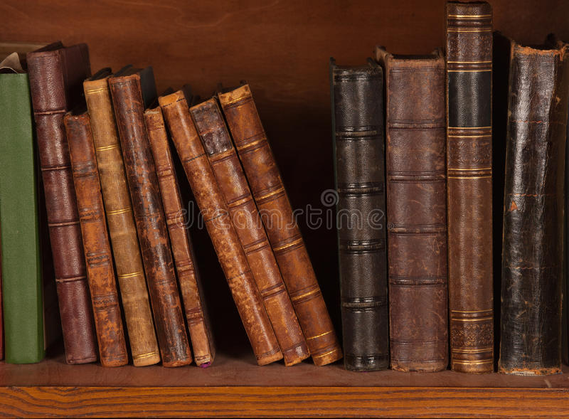 Libros antiguos en estante foto de archivo
