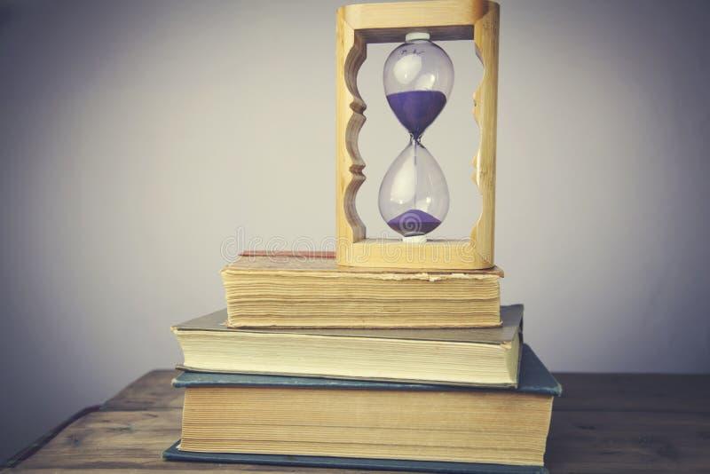 Libros con reloj de arena fotografía de archivo