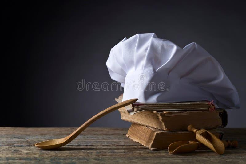 Libros culinarios viejos, sombrero del cocinero y cucharas de madera imagen de archivo libre de regalías