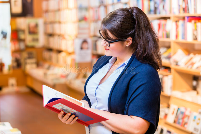 Libros de compra de la mujer en librería foto de archivo