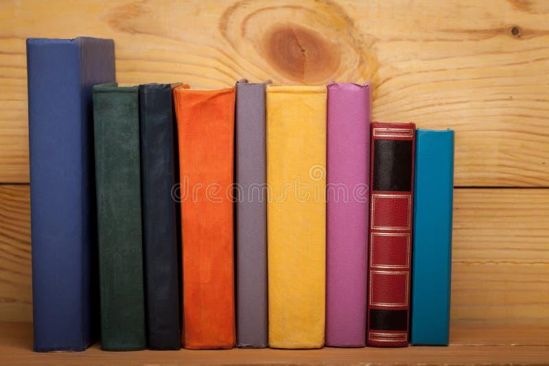 Libros de diversos colores en un estante de madera imagen de archivo