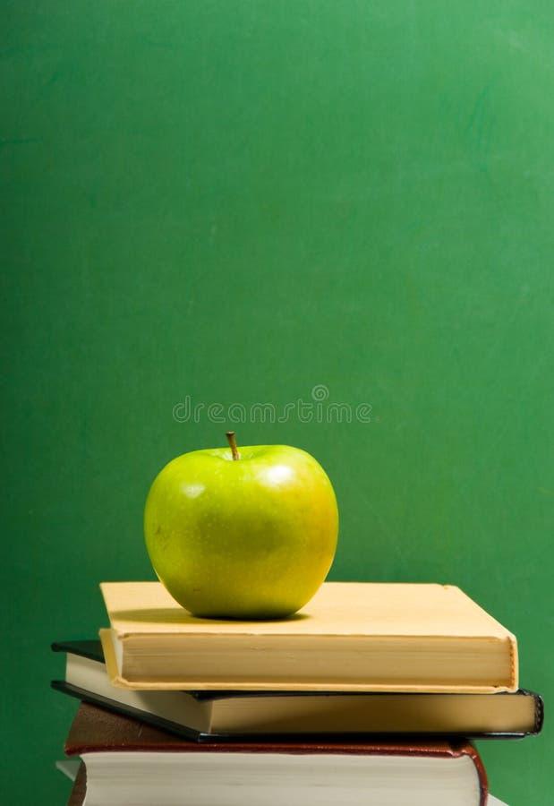 Libros de escuela con la manzana imagen de archivo