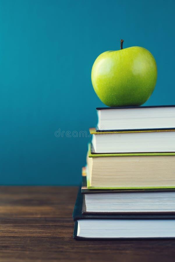 Libros de escuela con la manzana en el escritorio imágenes de archivo libres de regalías