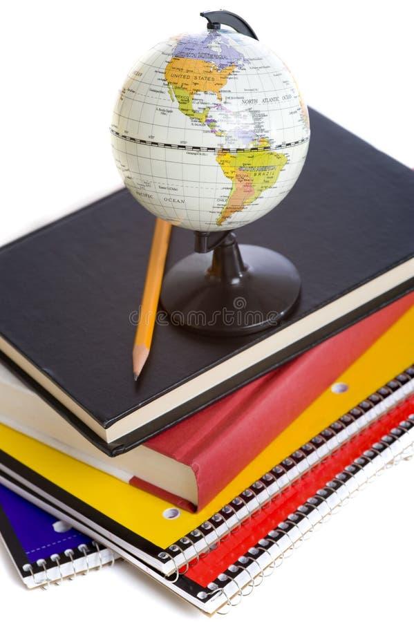 Libros de escuela y un globo miniatura fotografía de archivo libre de regalías