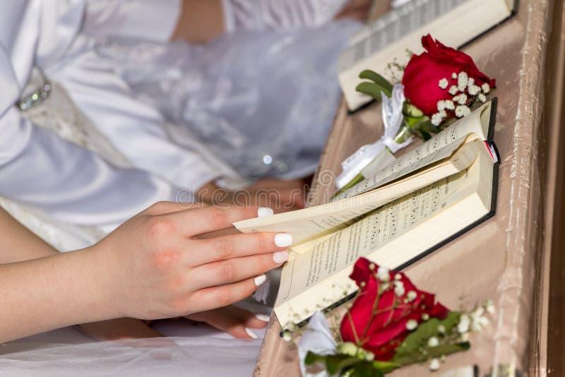 Libros de la muchacha de un himno de la tenencia en iglesia imagenes de archivo