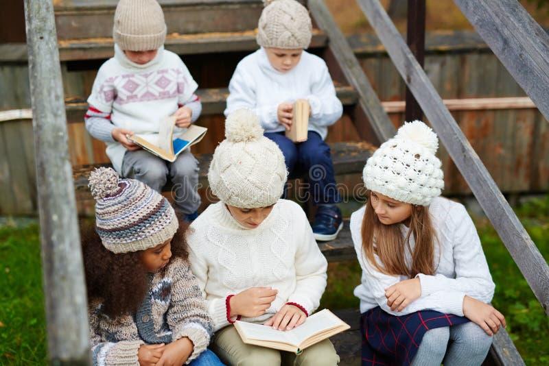 Libros de lectura de los niños al aire libre foto de archivo libre de regalías