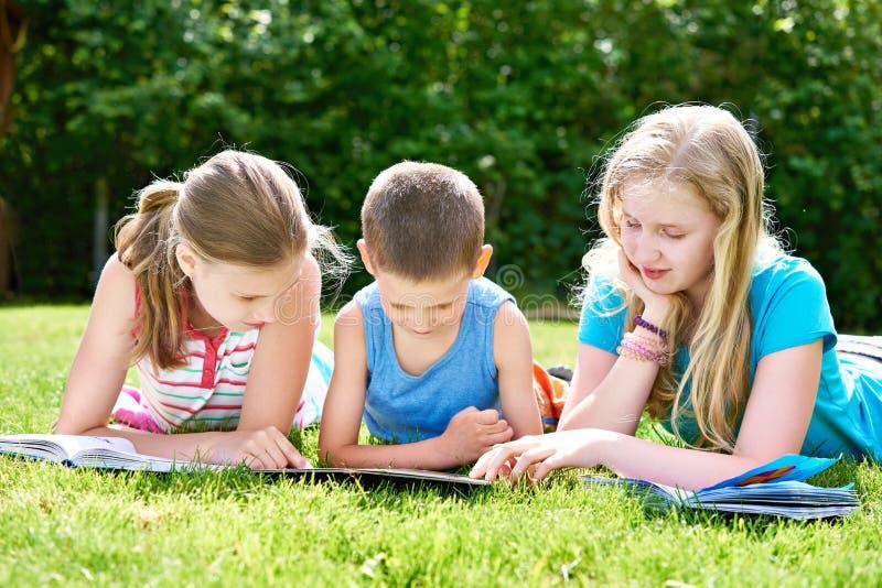 Libros de lectura de los niños de los amigos al aire libre en hierba imágenes de archivo libres de regalías