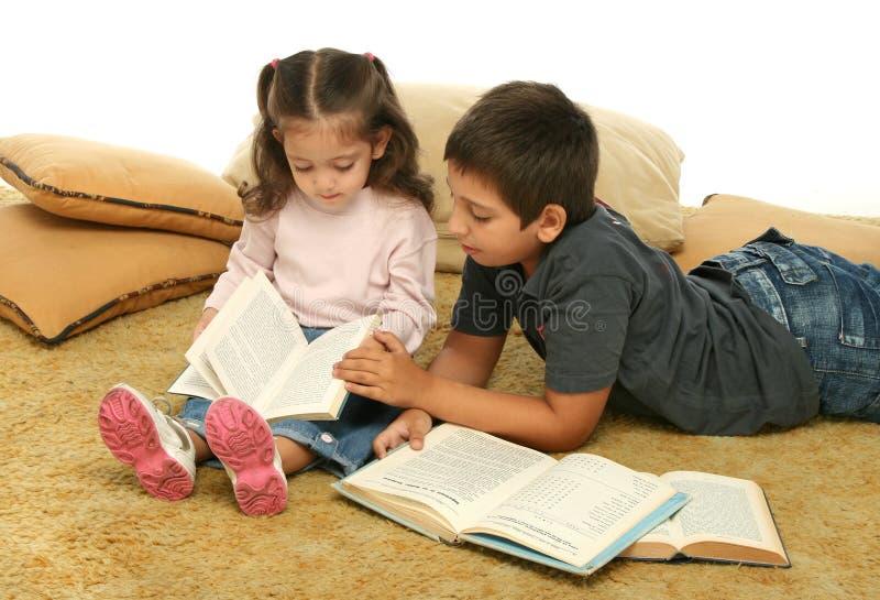 Libros de lectura del hermano y de la hermana en el suelo foto de archivo