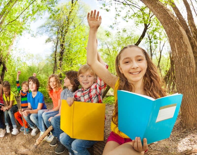 Libros de lectura felices de los niños al aire libre en el día soleado imagen de archivo libre de regalías