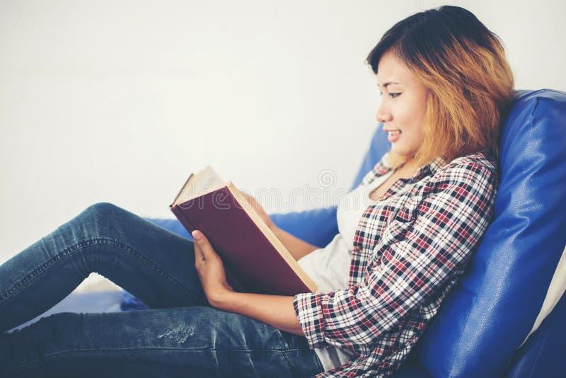 Libros de lectura de la mujer y mentira en sofá en casa fotos de archivo