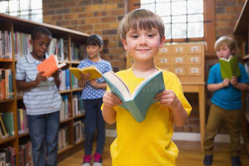 Libros de lectura lindos de los alumnos en la biblioteca imágenes de archivo libres de regalías