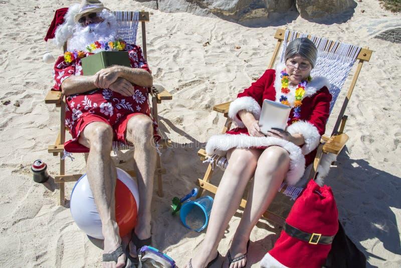 Libros de lectura de Papá Noel y de señora Claus y el tomar una siesta en la playa foto de archivo