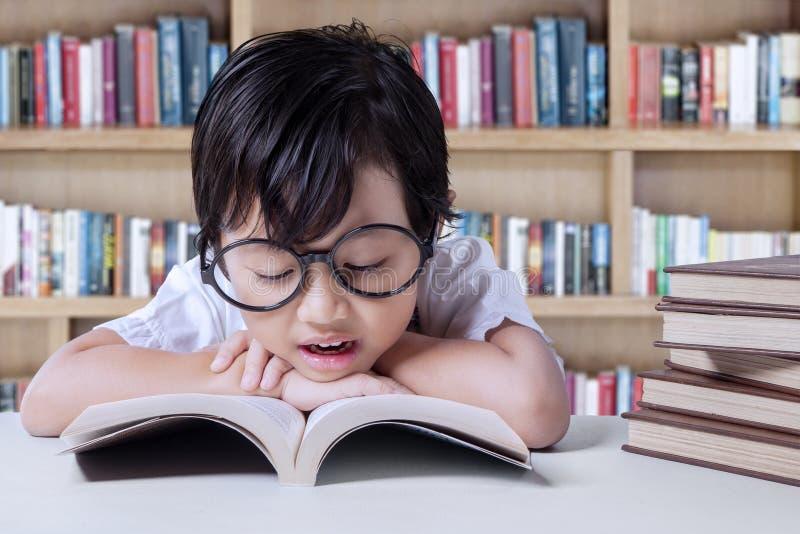 Libros de lectura preciosos de la niña en biblioteca foto de archivo