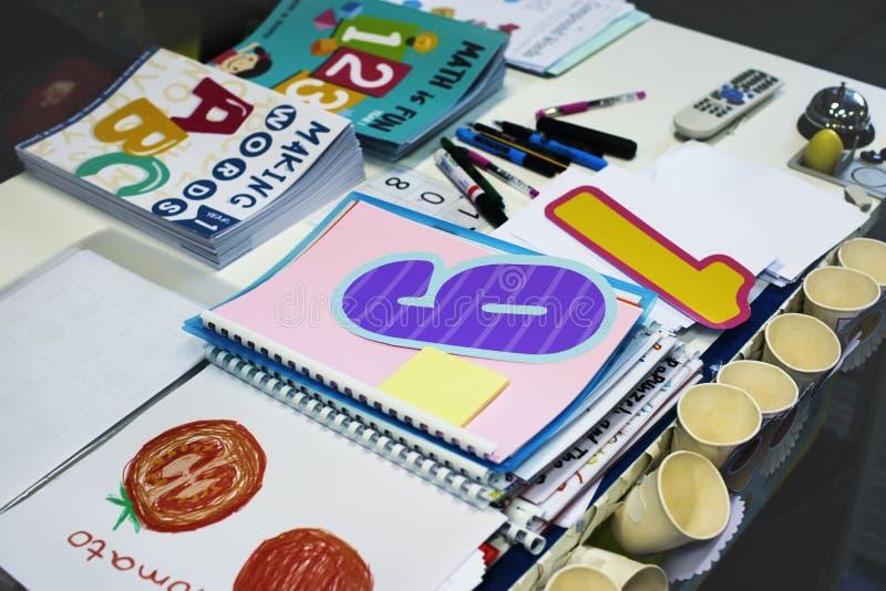 Libros de trabajo de los estudiantes de la guardería en el profesor Table foto de archivo libre de regalías