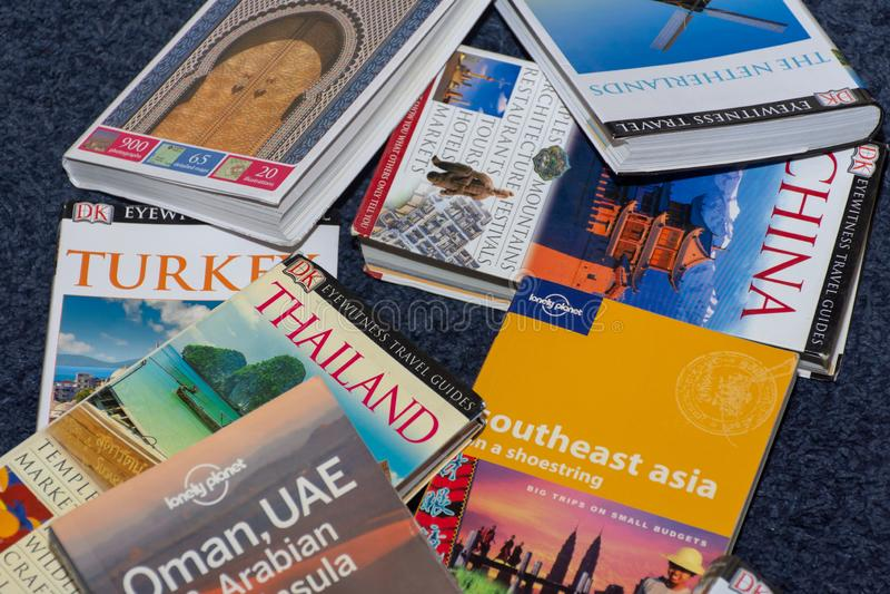 Libros del pa?s del viaje dispersados en el piso que busca para las vacaciones globales pr?ximas Tiempo de decisi?n fotos de archivo