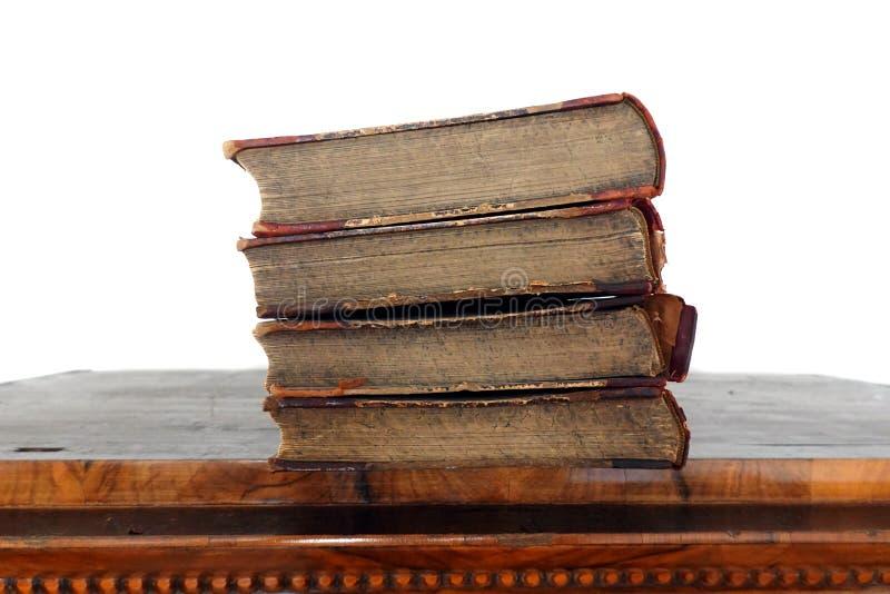 Libros del vintage en cubiertas dilapidadas en la vieja superficie de la tabla aislada foto de archivo libre de regalías