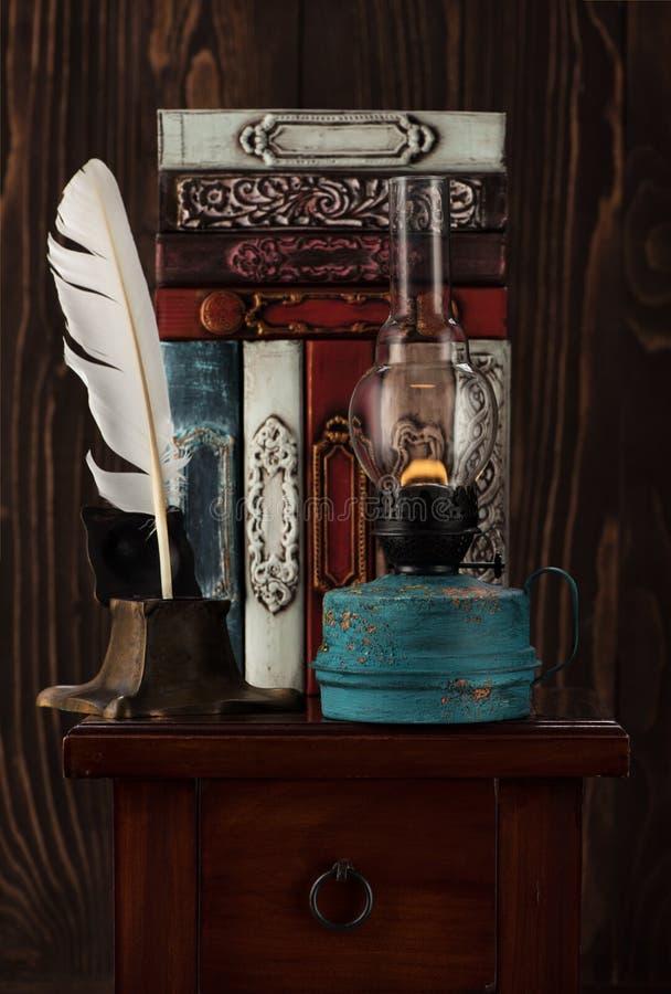Libros del vintage, lámpara de aceite vieja y tintero antiguo con una pluma imagen de archivo libre de regalías