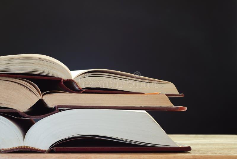 Libros en el escritorio con la pizarra foto de archivo libre de regalías