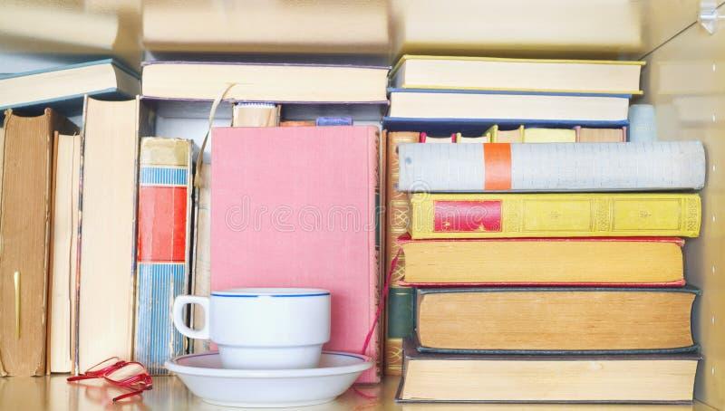 Libros en un estante de librería con la taza de café y de gafas Leyendo, aprendiendo, educación, concepto de la literatura, fotos de archivo libres de regalías